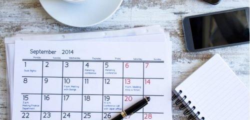 kalendarz długopis notatnik telefon i filiżanka na drewnianym blacie