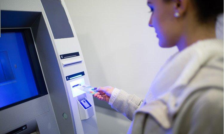 kobieta wsuwające kartę do bankomatu