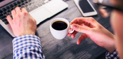 mężczyzna z kawą przy laptopie