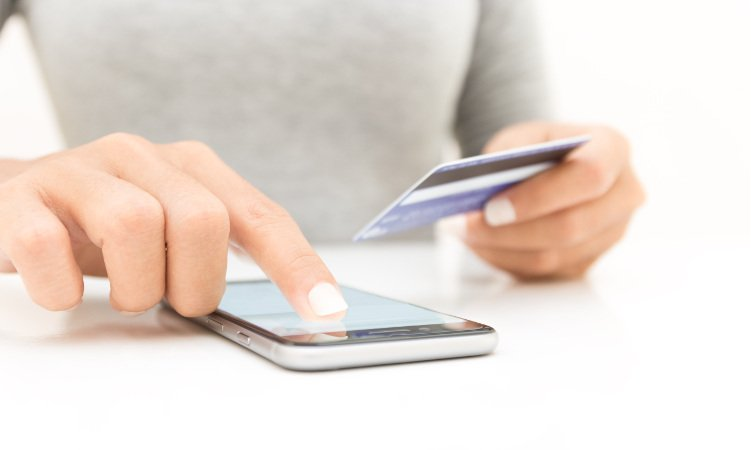 kobieta ze smartfonem i kartą kredytową