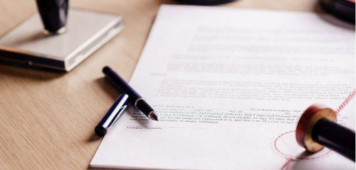 testament długopis i pieczątka na drewnianym blacie