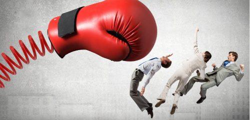rękawica bokserska na sprężynie uderzająca w trzy osoby w garniturach