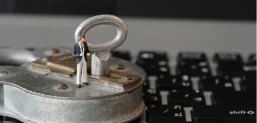 kłódka i miniaturka człowieka na klawiaturze