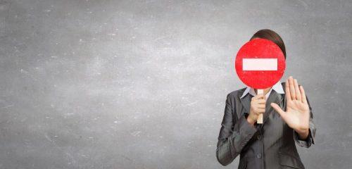 kobieta zasłaniająca twarz znakiem zakaz wjazdu