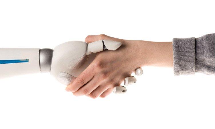 ludzka dłoń ściskająca dłoń robota