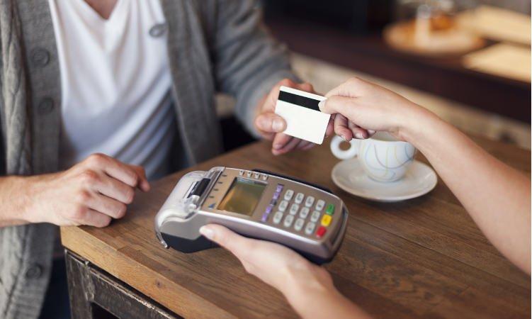 mężczyzna podający kobiecie kartę płatniczą w celu zapłaty