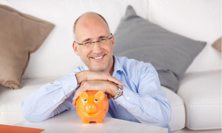 uśmiechnięty mężczyzna ze świnką skarbonką