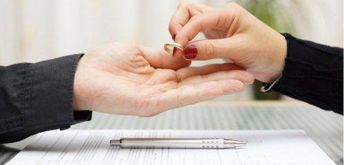 damska dłoń przekazująca obrączkę na męską dłoń