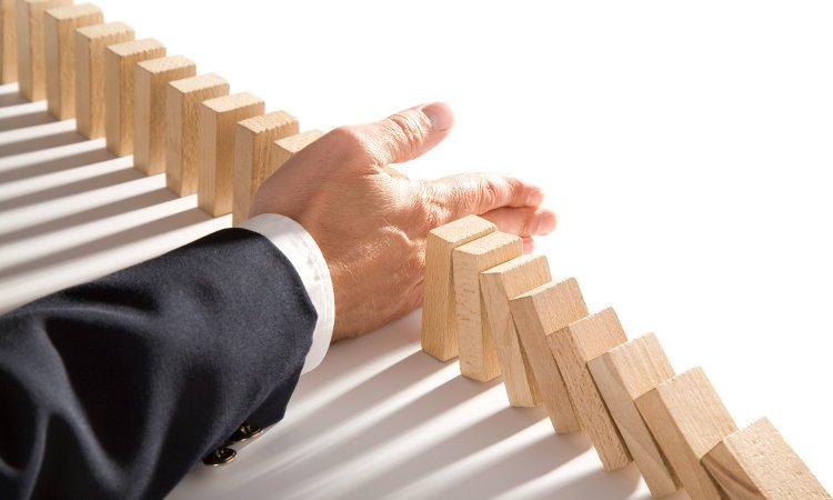męska dłoń zatrzymująca przewracające się domino