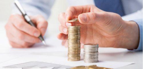 męska dłoń układająca słupki z monet
