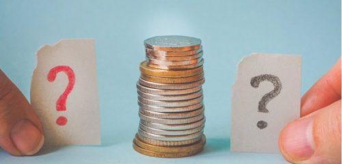 karteczki ze znakami zapytania przy stosie monet