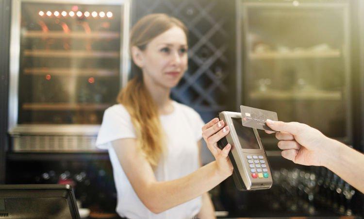 dłoń przykładające kartę płatniczą do terminala