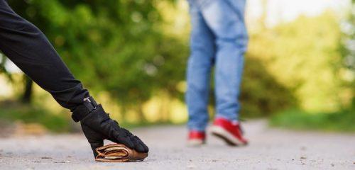złodziej zabierający z ulicy zgubiony portfel
