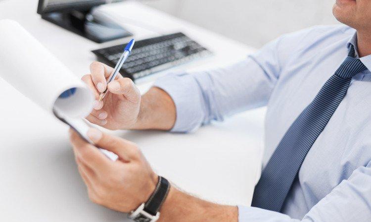 mężczyzna przy biurku z długopisem i kartkami papieru