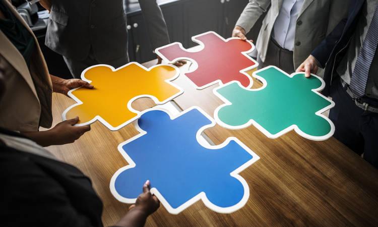 cztery osoby trzymające kolorowe puzzle nad blatem stołu