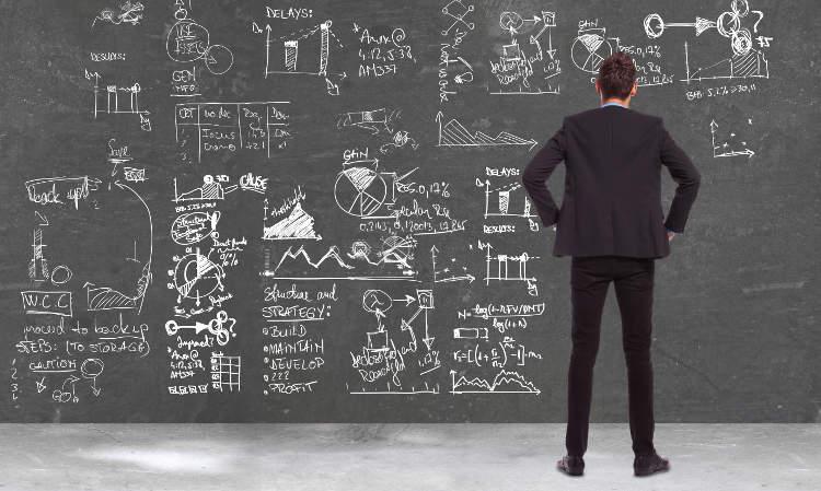 Mężczyzna przy czarnej tablicy z obliczeniami