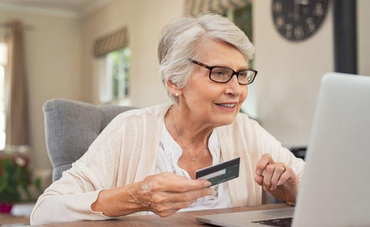 starsza pani z kartą płatniczą przy komputerze
