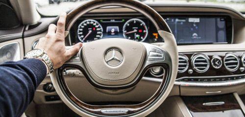 mężczyzna z drogim zegarkiem w luksusowym samochodzie