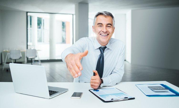 doradca kredytowy w biurze z wyciągniętą dłonią