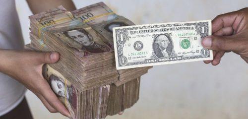 jeden dolar amerykański na tle bloku banknotów wenezuelskich
