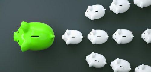 małe białe świnki skarbonki ustawione za dużą zieloną świnką skarbonką