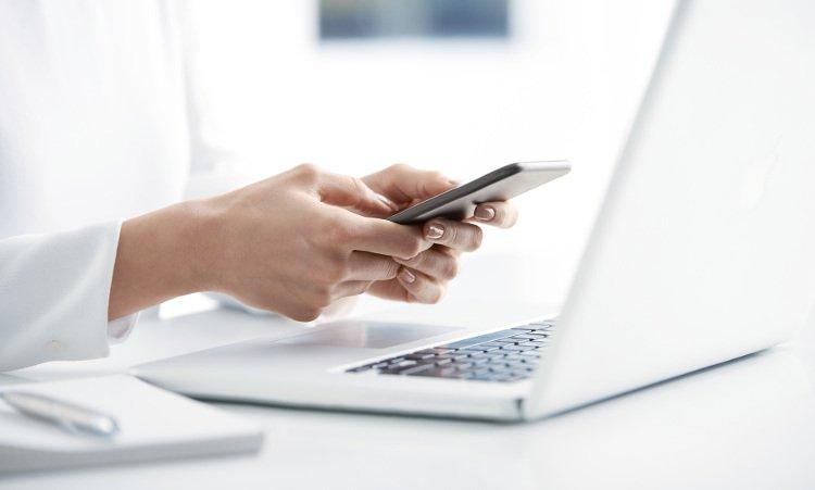 kobieta trzymająca samrtfon nad laptopem