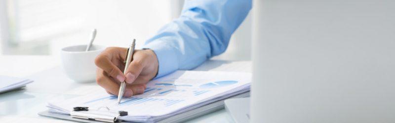 mężczyzna w niebieskiej koszuli wypełniający dokument