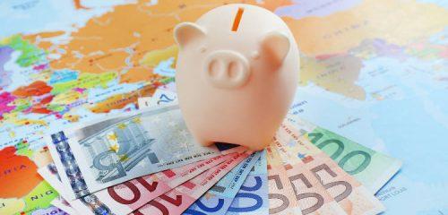 świnka skarbonka na pliku banknotów i mapie