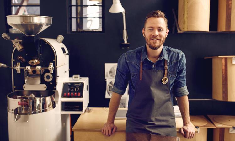 mężczyzna w fartuch na tle maszyny do palenia kawy