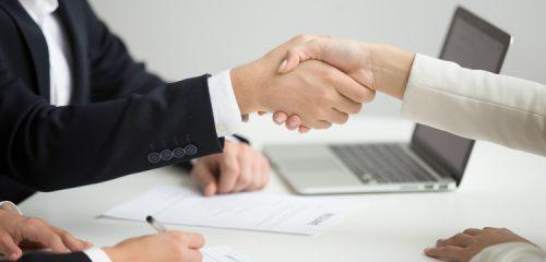 uścisk dłoni nad stołem z dokumentami i laptopem