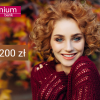 kobieta w fioletowym swetrze na tle liści