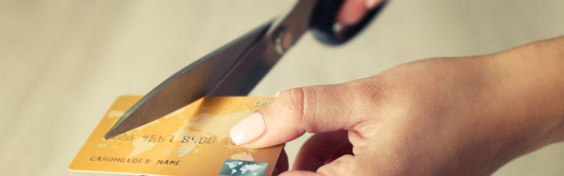damskie dłonie trzymające nożyczki i przecinające kartę kredytową