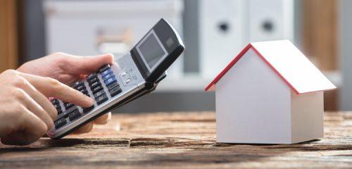 dłoń z kalkulatorem i makieta domu
