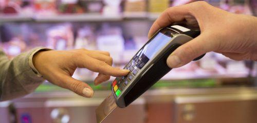 dłoń i terminal płatniczy z włożoną kartą