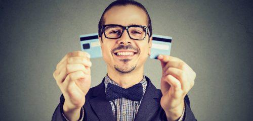 mężczyzna trzymający w dłoniach przeciętą kartę kredytową