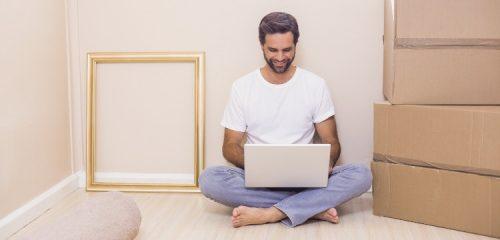 mężczyzna z laptopem siedzący na podłodze