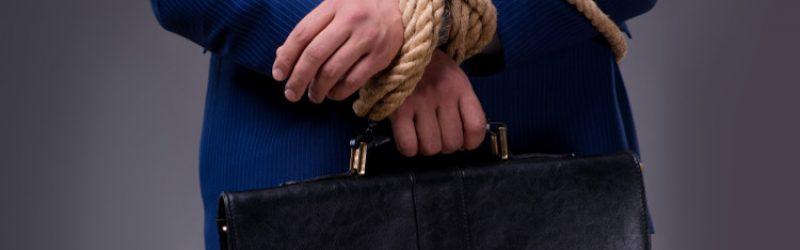 mężczyzna w niebieskim garniturze z aktówką i skrępowanymi rękami