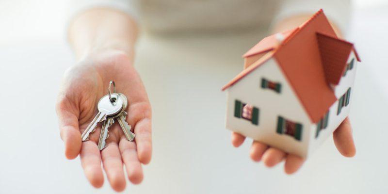 klucze i makieta domu na dłoniach kobiety