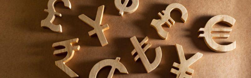 drewniane symbole różnych walut