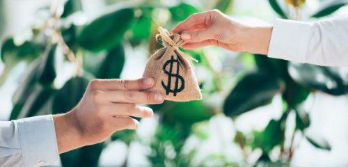 osoby przekazujące sobie woreczek z symbolem dolara