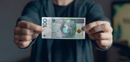 mężczyzna trzymający banknot stuzłotowy