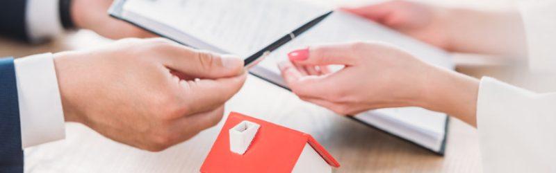 kobieta i mężczyzna podpisujący umowę i makieta domu na blacie