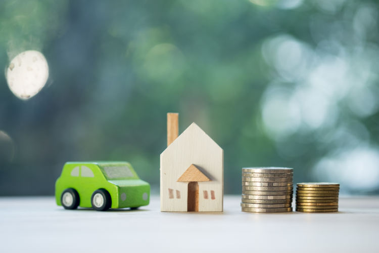 miniaturowy samochodzik, dom i dwa słupki z monet