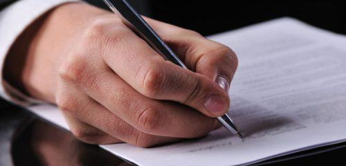 mężczyzna podpisujący długopisem dokument
