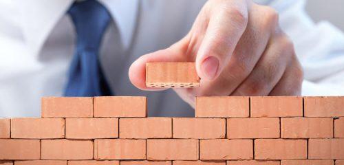 mężczyzna układający mur z cegieł