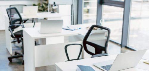 puste krzesła obrotowe przy białych biurkach