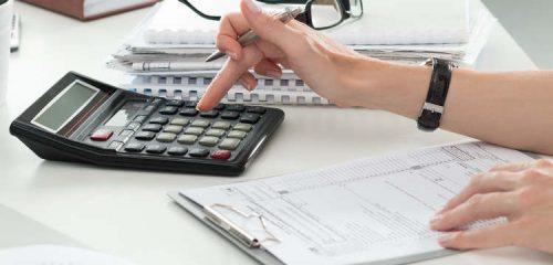 kobieta przy biurku z kalkulatorem