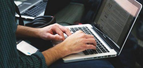 mężczyzna piszący na klawiaturze laptopa