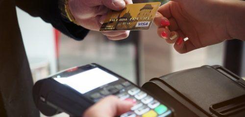 dwie osoby podają sobie kartę kredytową przed płatnością w terminalu