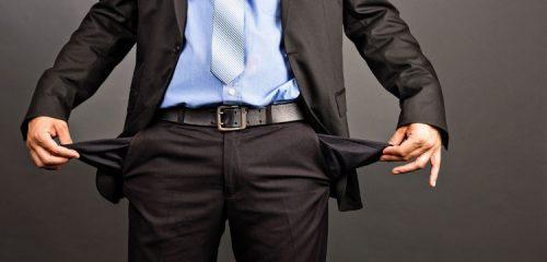 mężczyzna w garniturze pokazujący puste kieszenie
